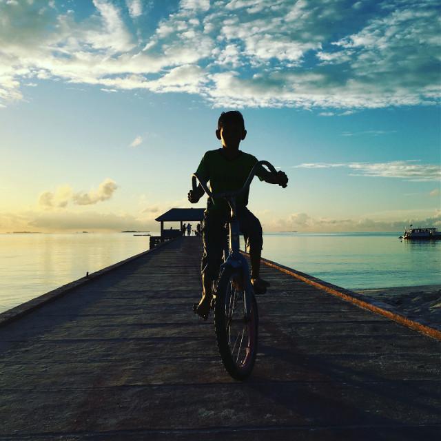 #maldives a young boy riding a bike on the jetty